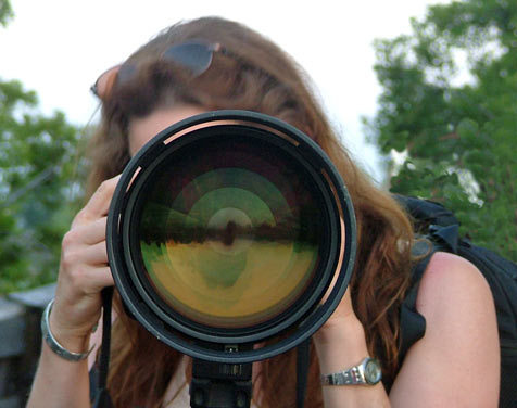 photographer behind the lens of her large camera on the boardwalk of Wakodahatchee Wetlands
